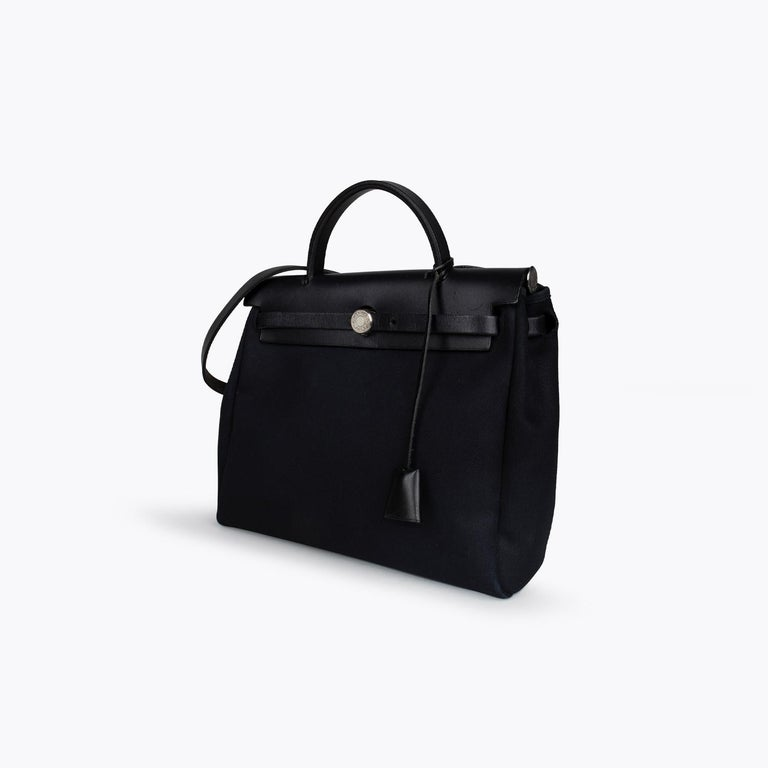 Black Toile Hermès Herbag PM with  – Palladium-plated hardware – Tonal Vache Hunter leather trim – Single flat top handle – Single flat shoulder strap, tonal Toile interior and logo pull-through closures at front flap  Overall Preloved Condition: