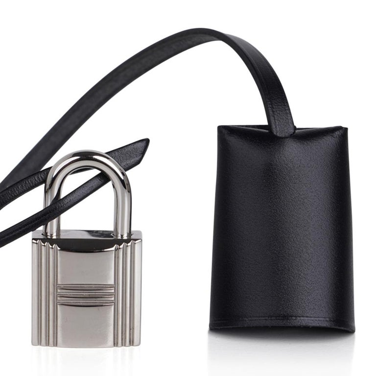 Guaranteed authentic Hermes Herbag Zip 31 featured in crisp black and white Criss Cross Toile and Black Vache Hunter cowhide leather. Signature Clou de Selle closure. Rear has an exterior Black canvas zip pocket. Interior has a matching removable