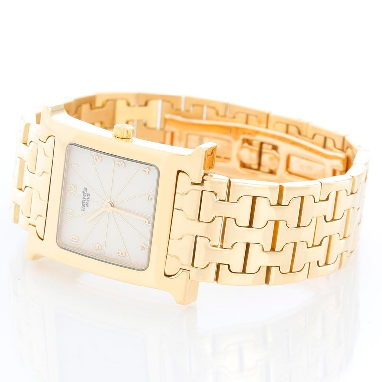 Hermes Heure H 18k Yellow Gold Ladies Watch HH1-585 - Quartz. 18K Yellow gold (26 mm x 35 mm ). White with Arabic numerals, sapphire crystal. 18K Yellow gold bracelet; will fit up to a 7 inch wrist . Pre-owned with custom box.