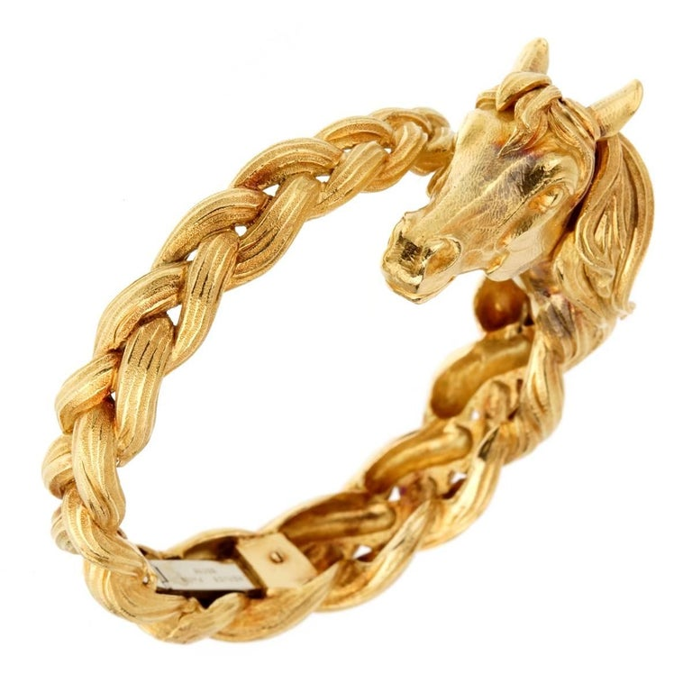 A magnificent Hermes bangle depicting a horse head and mane in 18k yellow gold. The bracelet weighs 117.3 grams.  Sku: 916