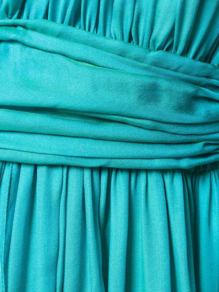 The silk-satin of this Hermès gown is quite mesmerising – its vivid turquoise hue has an iridescent green lustre that moves with the light. This dress has a V-neckline with ruching along the bodice that flows into a floor-sweeping skirt. The back is
