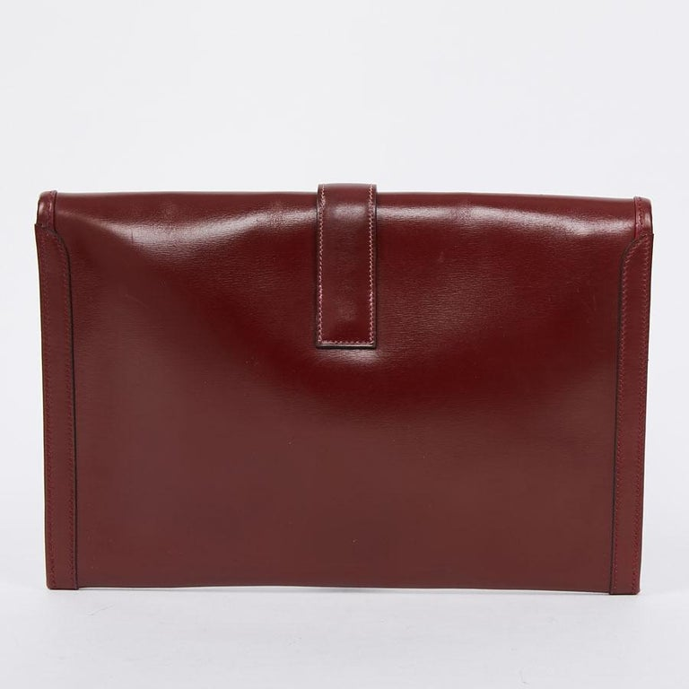 We no longer present it ... The Jige clutch in red box leather H size medium from the House of HERMES is a timeless one. Clasp H in relief with white stitching. Fabric interior. Slight dark mark on the front on the tongue of the bag. The black spot