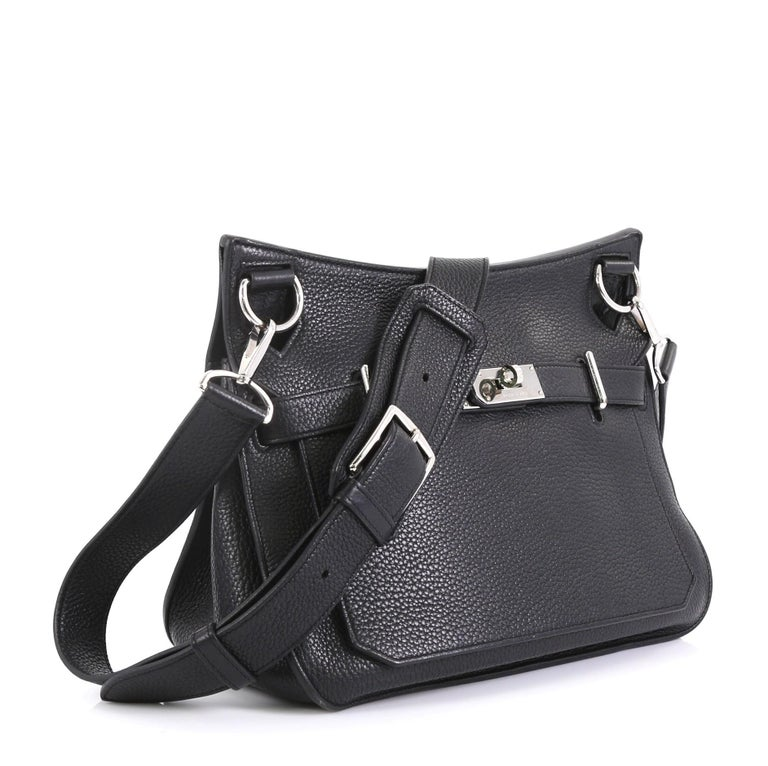 This Hermes Jypsiere Handbag Clemence 28, crafted in Noir black Clemence leather, features a long adjustable strap and palladium hardware. Its front flap with the turn-lock closure opens to a Noir black Chevre leather interior with slip and zip