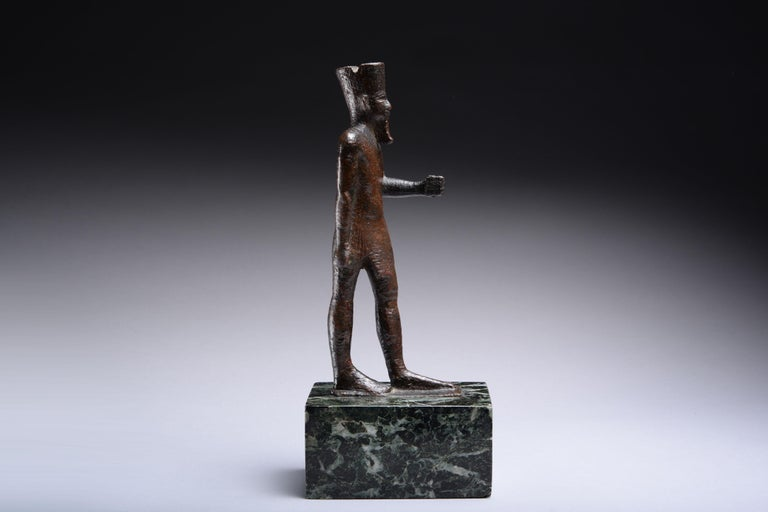 A large bronze figure of the Great Theban King of the Gods, Amun. Dating to Egypt's Late Period, circa 664-332 BC.   Solid cast, the god depicted striding forward on his left leg, wearing a false beard, conical headdress and pleated kilt, his
