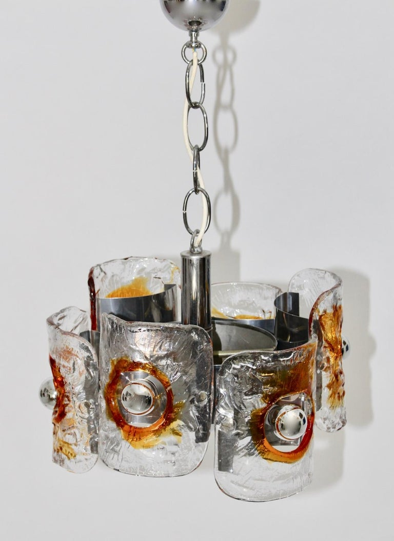 This chandelier by Mazzega, Italy, 1970 has a chromed metal construction and four yellow and clear glass shades. The chandelier lights with six E 14 bulbs. To hang up with a chain  approx. measures: Diameter 43 cm Height 62 cm.