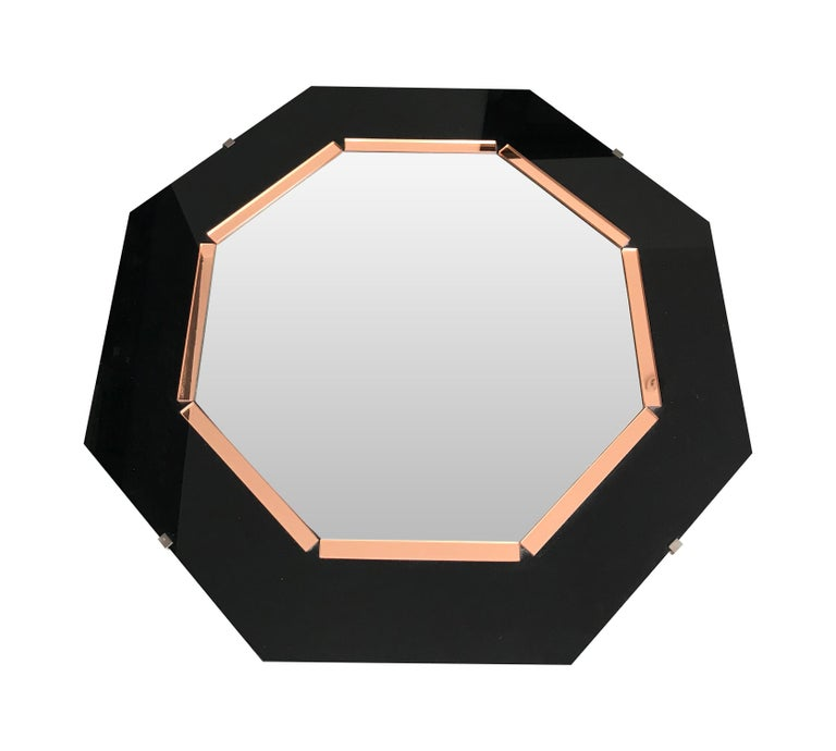 An Art Deco style octagonal mirror with black glass surround and rose mirror interior frame around a bevelled mirror and mounted on board.