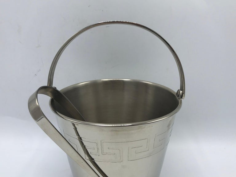 Listed is a beautiful, 1970s chrome ice bucket and tongs. The piece has a lovely stamped greek-key motif along the border of the bucket. 
