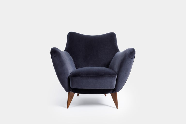 Sculptural and elegant 'Perla' armchair by Guglielmo Veronesi for ISA Bergamo. Slightly curved back with gently outstretched arms ending in distinctly tapered legs. Fully restored and reupholstered in navy velvet upholstery.  Literature: Domus,