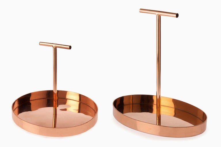 Phil is a family of metallic trays designed by Indian designer Bojou Jain. This model of Phil is conceived in copper-plated metal with an oval base. At the center of the base rises a high T-shape handle, a non-conventional element that makes this