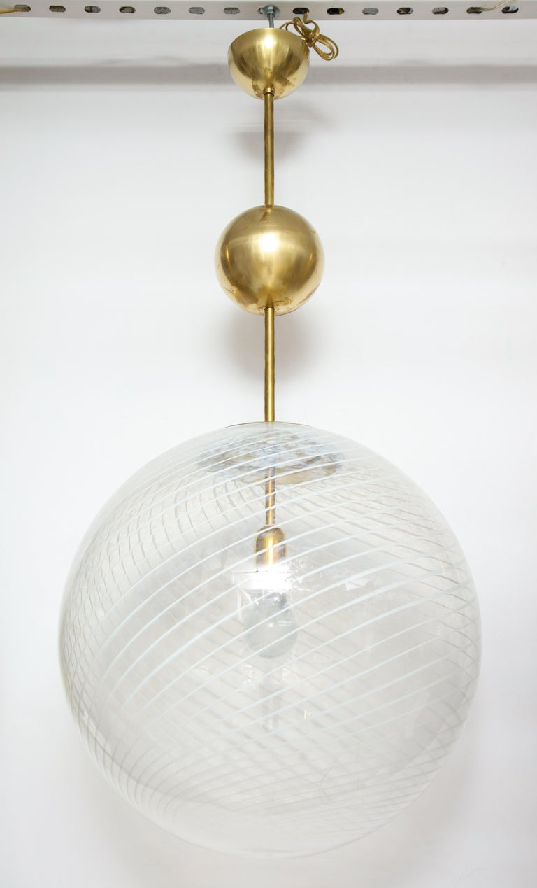 A large Venini mottled white and clear handblown Murano glass globe with a cross-hatched pattern suspended from the original stem with brass ball adornment below the canopy, newly wired for the American market with a single Edison socket that can