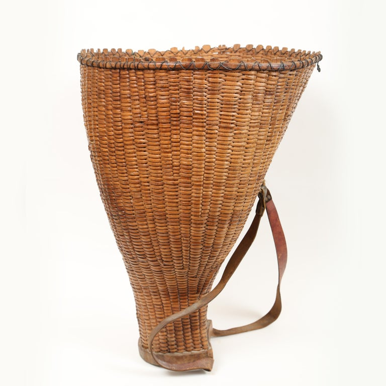 Large 19th century French handwoven grape pickers basket. The leather straps are for carrying the basket on your back. The vertical strapping terminates in the thick wooden bottom. The baskets wonderful form fitting shape is strengthened with wire.