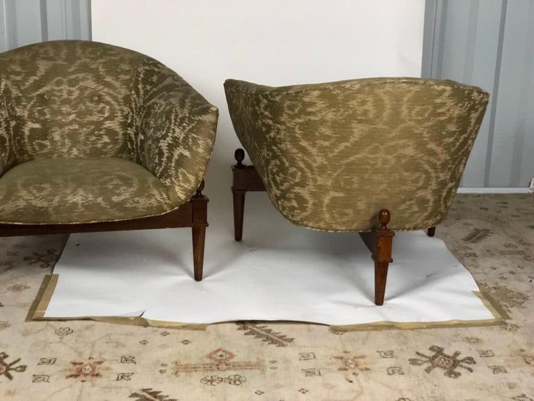 Pair of midcentury style Mimi club chairs on wooden tripod platforms with upholstered tufted seats. Made by Global Views. Measures: Seat height is 16 inches and the arm height is 23 inches.
