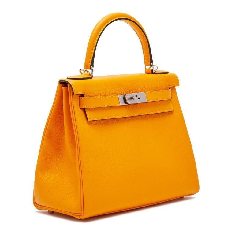 This Hermès Kelly exudes opulence, crafted in a eye-catching shade of Apricot and lined in a complementary toned goatskin and finished with brushed metal palladium hardware. Compact-sized, the handbag's interior holds a zipped pocket and an open