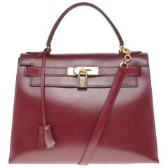 Hermès Kelly 28cm sellier with strap handbag in burgundy calfskin, Gold hardware