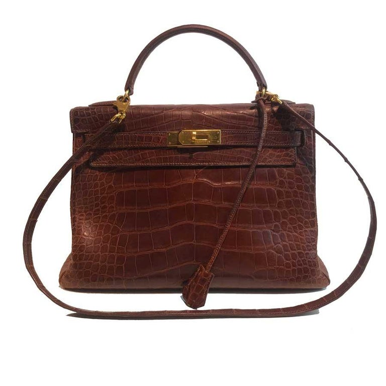 Kelly from Maison Hermès in size 32 cm, it is in a mat brown alligator and its jewelry is in gold metal. It has its shoulder strap measuring 90 cm, more for carrying on the shoulder than cross body. This kelly bag has its alligator bell with the two