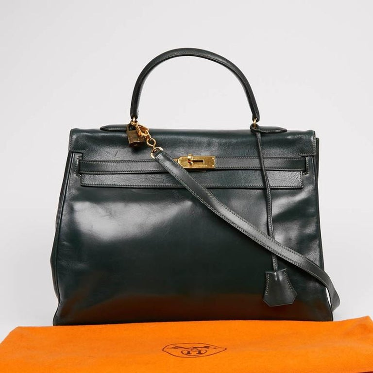 The essential Kelly 35 bag from Maison Hermès in green box leather. The jewelry is made of gold metal. It will be delivered with its padlock, zipper, bell and keys. It can be carried in the hand as well as on the shoulder using a removable strap. It