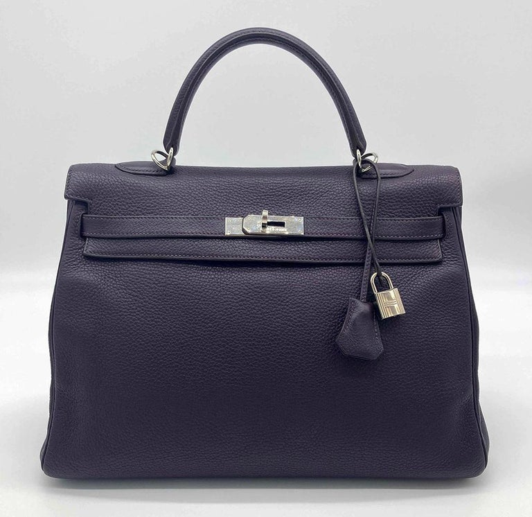 Hermes purple raisin kelly 35 in excellent condition. Deep purple raisin clemence leather exterior trimmed with silver palladium hardware. Signature twist lock double strap top flap kelly closure opens to a matching purple leather interior with one