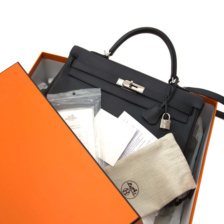 Very Good Preloved Condition   Hermes Kelly 35 Retourne Ardoise Swift PHW   This treasure is a bag to covet!  Skip the waiting list and get your hands on this exquisite and iconic Hermès Kelly in Ardoise Swift leather.  Retourne is known for its
