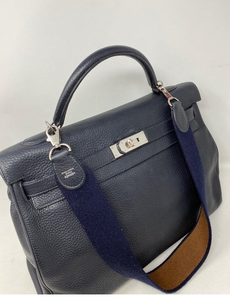 Hermes Kelly 40 Blue Indigo Bag. Palladium hardware. Navy and tan canvas strap. Good condition. Large size Kelly bag. Can be worn with or without strap. Includes clochette, lock, keys and dust cover. O stamp. Guaranteed authentic.