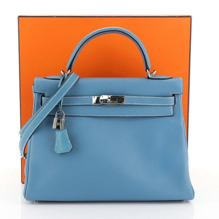 This Hermes Kelly Handbag Bleu Jean Clemence with Palladium Hardware 32, crafted in Bleu Jean blue Clemence leather, features a single rolled top handle, protective base studs, and palladium hardware. Its turn-lock closure opens to a Bleu Jean blue