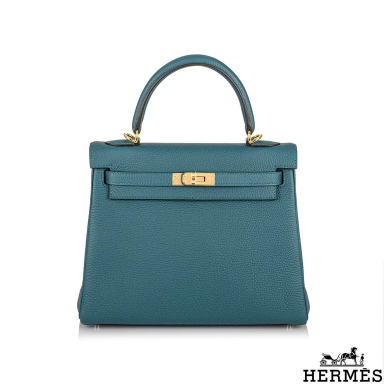 An exquisite Hermès Kelly II Retourne 25cm Vert Bosphore Handbag. The vivid vert bosphore colour is complimented with gold hardware. The exterior of this Kelly features a Retourne style in vert bosphore togo leather. It has a front toggle closure, a