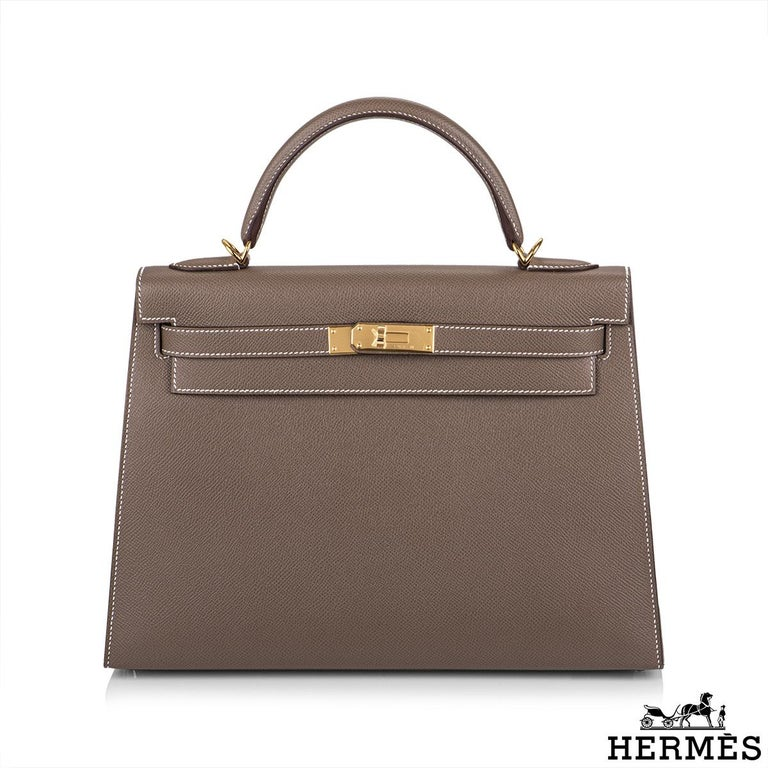 An exquisite Hermès Kelly II Sellier 32cm Epsom Etoupe handbag. The exterior of this Kelly features a sellier style in etoupe epsom leather. The etoupe epsom leather is complimented with gold hardware and contrast white stitchings. It features a