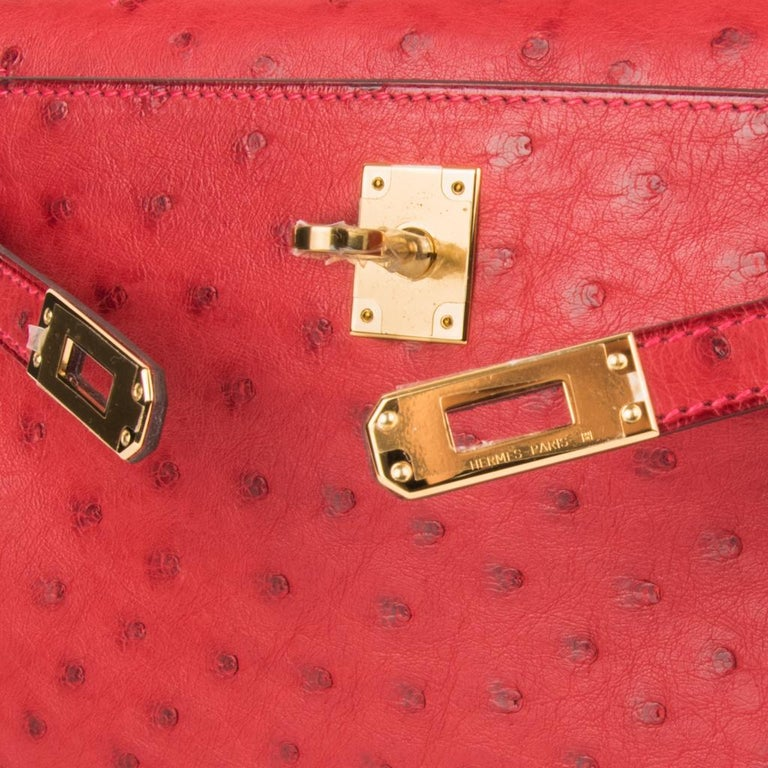Guaranteed authentic Hermes Kelly pochette bag features Rouge Vif Ostrich. This beautiful Hermes clutch is accentuated with gold hardware and the signature pink top stitch. Signature stamp on interior. Small interior compartment. Comes with sleeper.