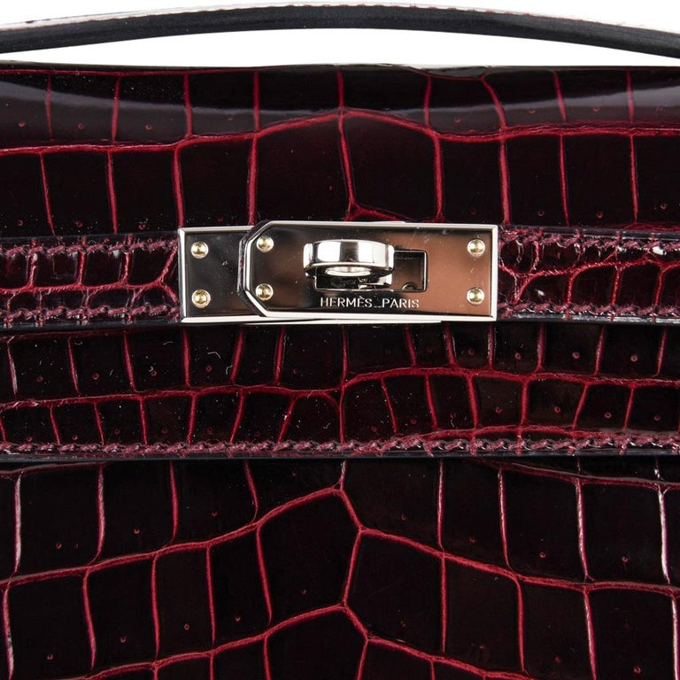 Guaranteed authentic exquisite jewel toned Hermes Kelly  Pochette clutch bag featured in rich Bordeaux lisse crocodile. Fresh with Palladium hardware. Stamped HERMES MADE IN PARIS on the interior. Small interior compartment. Comes with sleeper and