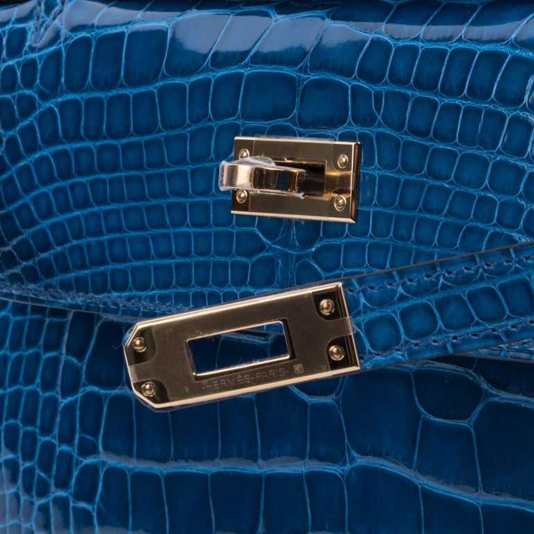Guaranteed authentic Hermes Kelly pochette features blue Mykonos alligator. This exquisite, rich blue is neutral and takes you from day to evening in one step. Lush with gold hardware. Signature stamp on interior. Small interior compartment. Comes