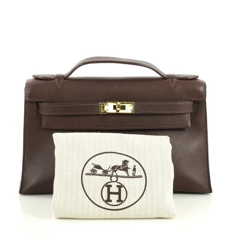 This Hermes Kelly Pochette Swift, crafted in Chocolate brown Swift leather, features top flat handle, frontal flap, and gold hardware. Its turn-lock closure opens to a Chocolate brown Swift leather interior with slip pocket. Date stamp reads: K
