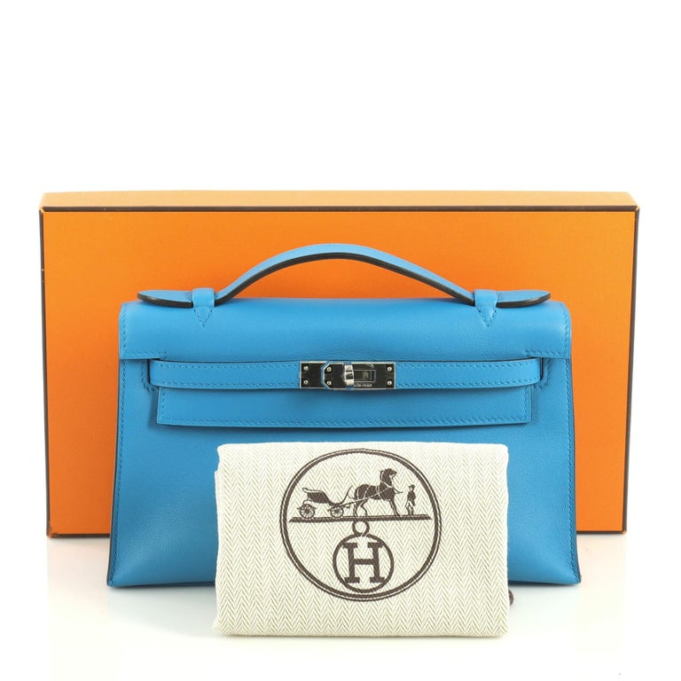 This Hermes Kelly Pochette Swift, crafted in Bleu Zanzibar blue Swift leather, features top flat handle, frontal flap, and palladium hardware. Its turn-lock closure opens to a Bleu Zanzibar blue Swift leather interior with slip pocket. Date stamp