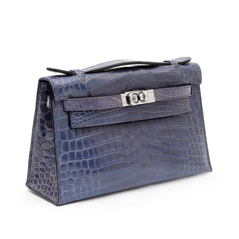 Inspired by Hermès' Kelly tote bag, designed with the iconic details of it's big sister and meticulously crafted from a shiny, rich and opulent Brighton Blue Crocodile leather, this miniature Hermès Kelly Pochette clutch bag is sure to make a