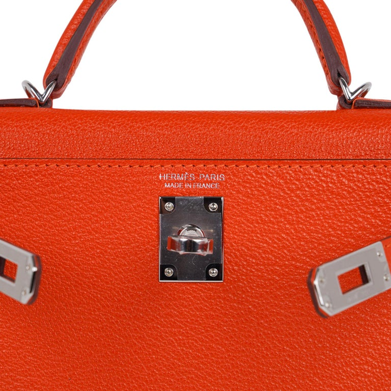 Guaranteed authentic Hermes Kelly 20 Mini Sellier bag featured in vibrant orange Feu with gentle pink Rose Eglantine interior.  Coveted Chevre leather accentuated with Palladium hardware. Comes with signature Hermes box, shoulder strap, and