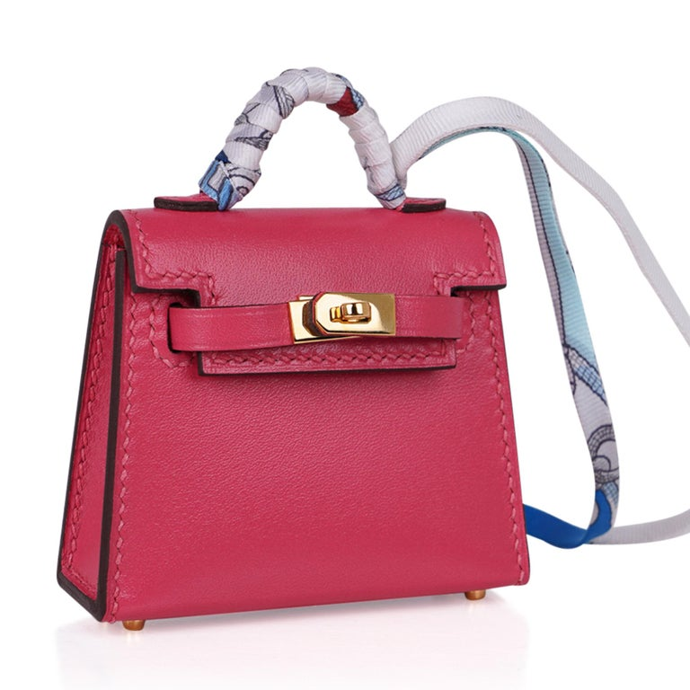 Guaranteed authentic very rare limited edition Hermes Kelly Twilly Bag Charm features a miniature Kelly in Rose Lipstick. Shaped like a Kelly Bag crafted in amazing detail. The charm has Gold Hardware and a wrapped handle in a silk print
