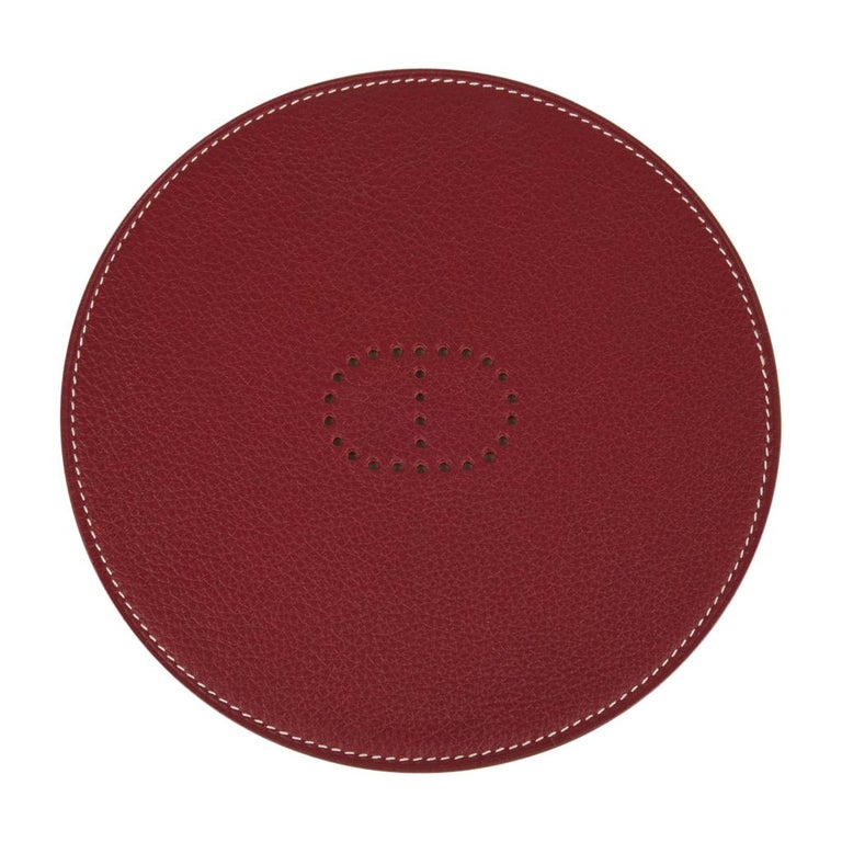 Guaranteed authentic Hermes Kezako round mini pad for the desk. Features taurillon leather bi color Rouge H and Gold with perforated Chaine d'Ancre detail center. Lovely luxury gift idea! New or Store Fresh Condition final sale  CASE