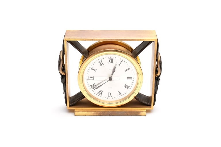 A fine Hermes clock with a gold-plated brass case with leather belt buckles. Roman numeral dial, quartz movement.   1970s  Marked on dial.  Measures: 6.25