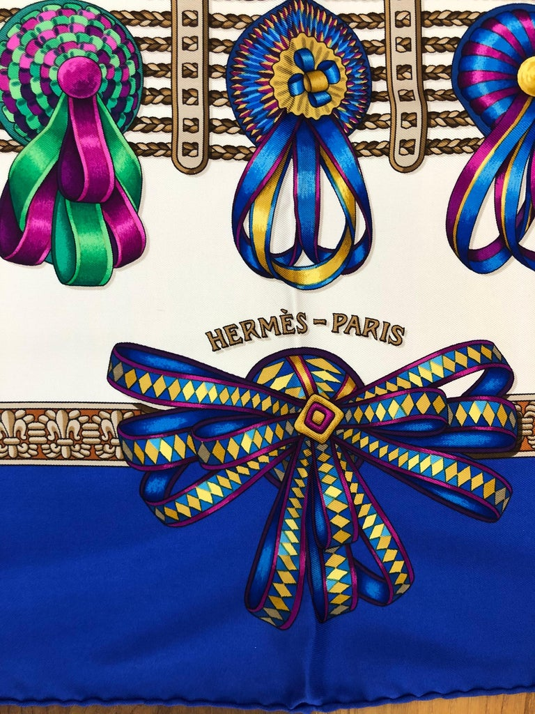 1993 silk scarf designed by Joachim Metz, the scarf is in excellent condition. The graphics feature very colorful equestrian ribbons over a white background and a blue border. The hand rolled hems are nice and plump, and the care tag intact. This
