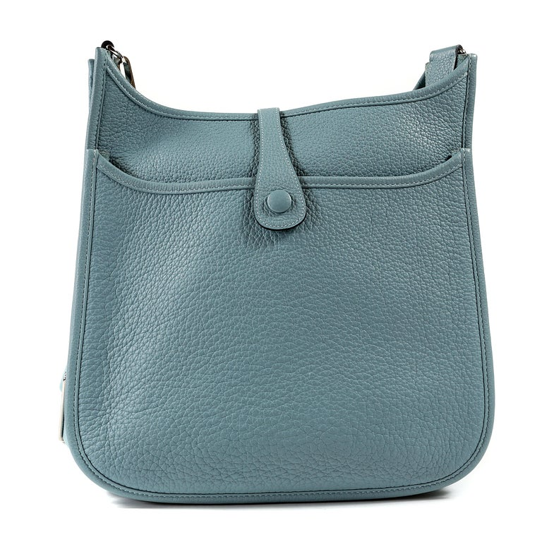 This authentic Hermès Light Blue Clemence Medium Evelyne PM III is in pristine condition. Extremely sought after, the Evelyne is an understated day bag that is stylish and practical.  The third generation sports a rear pocket and adjustable canvas