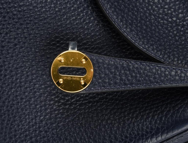 Guaranteed authentic Hermes Lindy 26 bag featured in rich Blue Nuit.  Super chic  in Clemence.   Lush with gold hardware.  This versatile bag can be carried by hand, or shoulder.   Spacious interior with an interior pocket on each side.   Top has