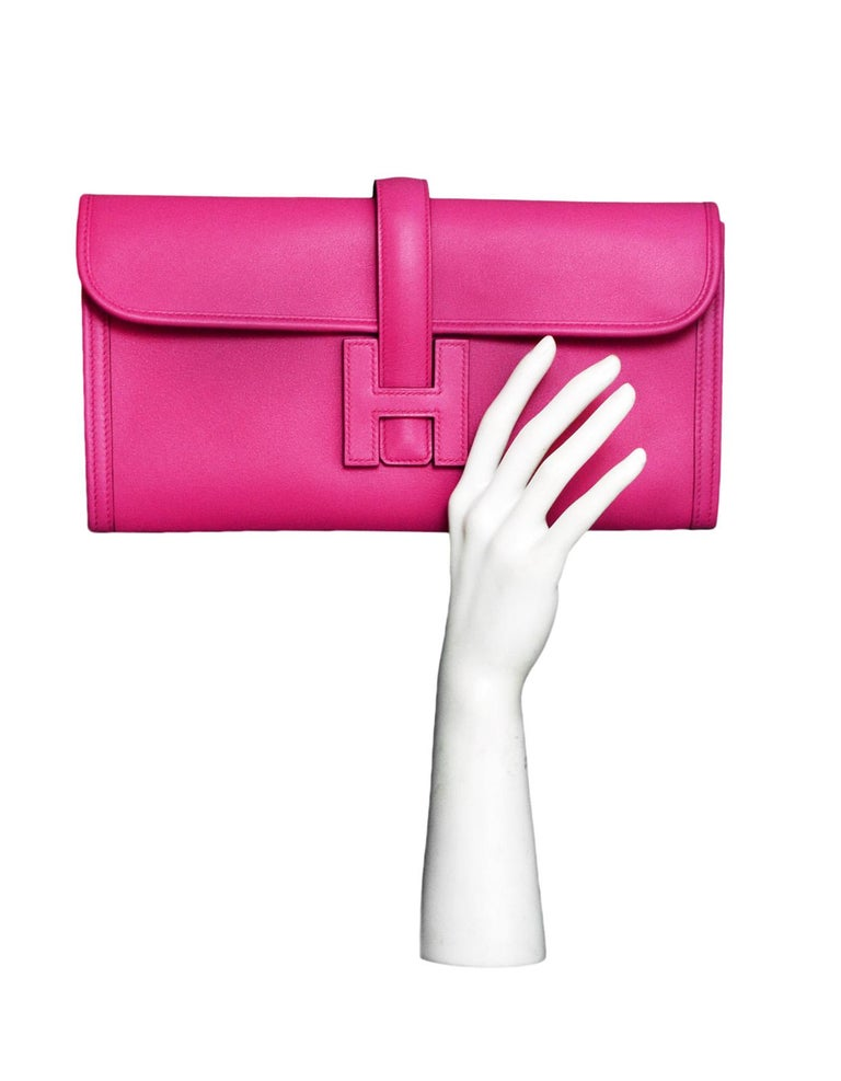 Hermes Magnolia Swift Leather Jige Elan 29 Clutch Bag  Made In: France Year of Production: 2018 Color: Magnolia pink Hardware: None Materials: Swift leather Lining: Leather Closure/opening: Flap top with strap that goes through H Exterior Pockets: