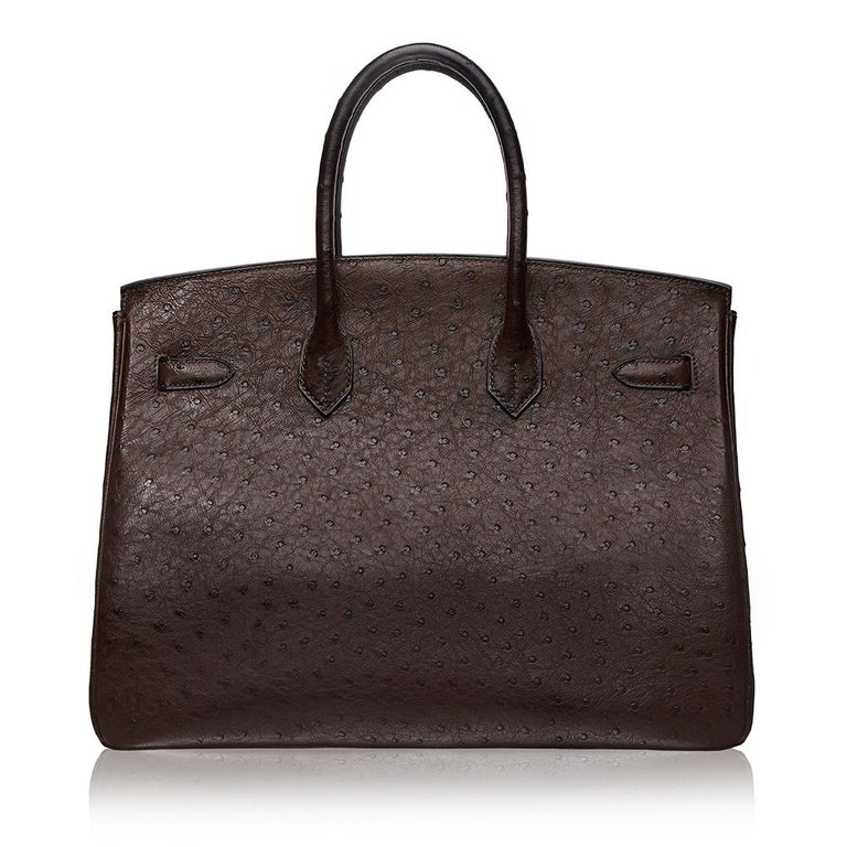In a beautiful and earthy-toned shade of Marron Fonce Brown, this 35cm Birkin bag from Hermès is a true testament to the quality of the house's craftsmanship, exuding timeless style and elegance, perfect for any occasion. It is crafted from Ostrich