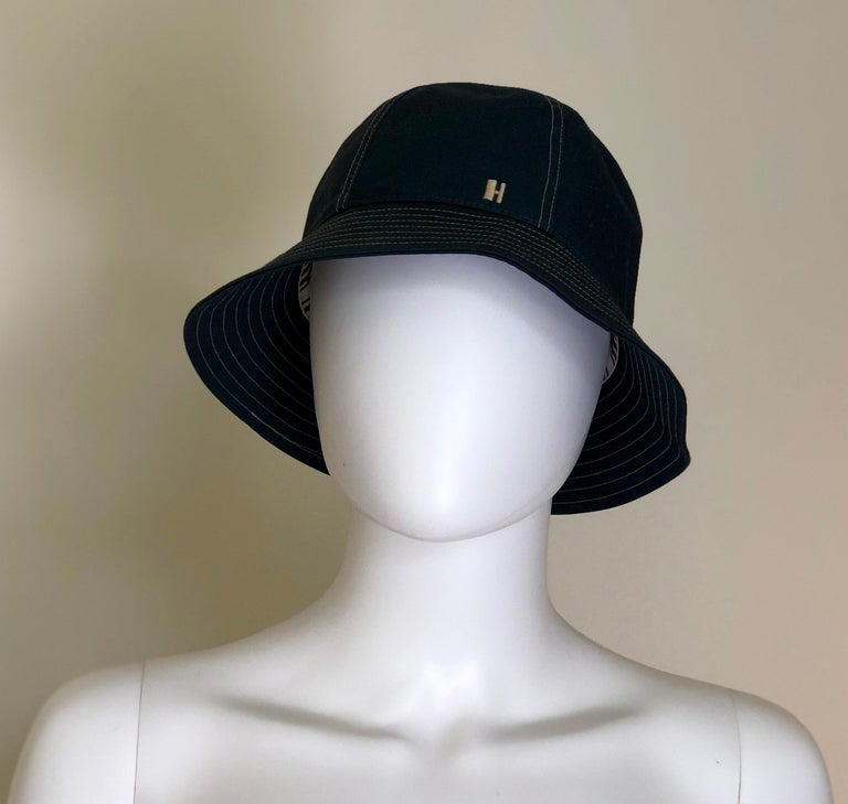 Offered is a signed Hermes Size 57 midnight blue (dark blue-jean blue) cotton bucket (cloche) hat with a tan circular multi-row top stitch design on the brim and underneath the brim.  The interior rim is bordered with a white wide grosgrain ribbon