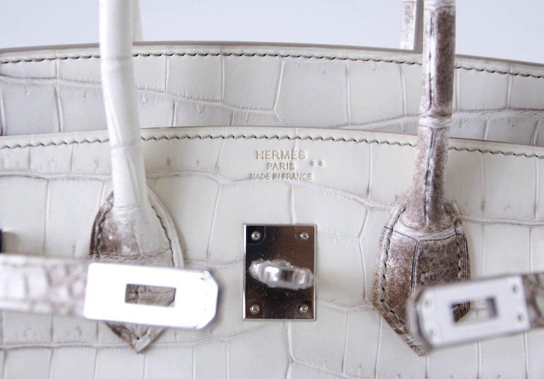 The Crème de la Crème of Hermès.  The most prized Hermes Birkin in the world, this beautiful white Hermes Birkin 25 Himalayan boasts spectacular Crocodile Niloticus skin. Brand new with all original accompaniments, this rare beauty is unlike any