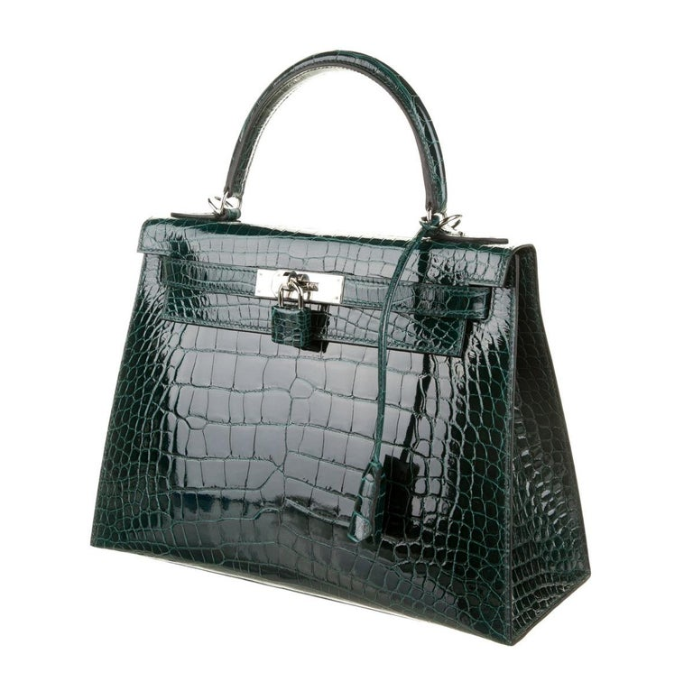 • Alligator • Palladium tone hardware • Leather lining • Turn-lock closure • Made in France • Date code present • Handle drop 3.5