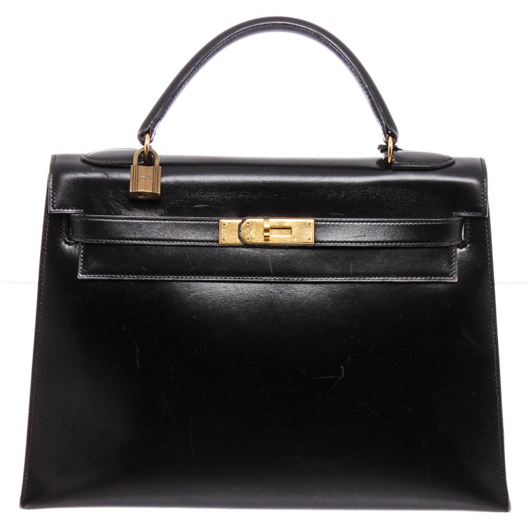 Noir Box leather Hermès Kelly Sellier 32 with gold-plated hardware, single rolled top handle, single detachable flat shoulder strap, protective feet at base, tonal chevre interior, three interior pockets; one with zip closure and belted turn-lock
