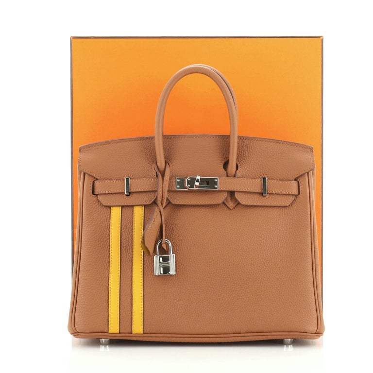 This Hermes Officier Birkin Handbag Limited Edition Togo with Swift 30, crafted in Gold brown Togo and Jaune Ambre brown Swift, features dual rolled handles, frontal flap and palladium hardware. Its turn-lock closure opens to a Bordeaux burgundy