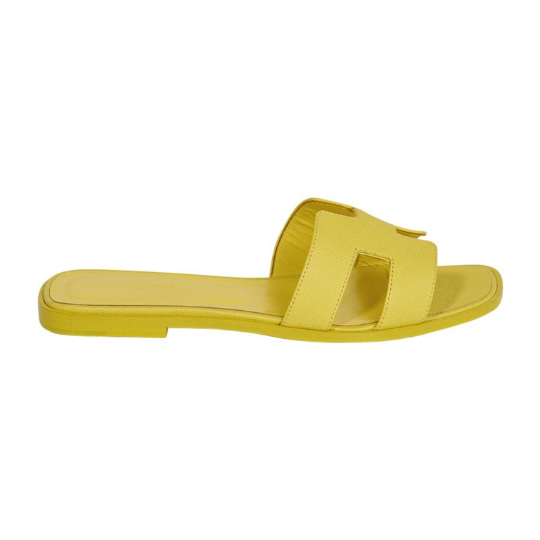 Guaranteed authentic Hermes Oran sandel shoes featured in vivid Lime Epsom leather. The iconic top stitched H cutout over the top of the slide in Epsom. Matching embossed calfskin insole.  Wood heel with leather sole.  Comes with sleepers and
