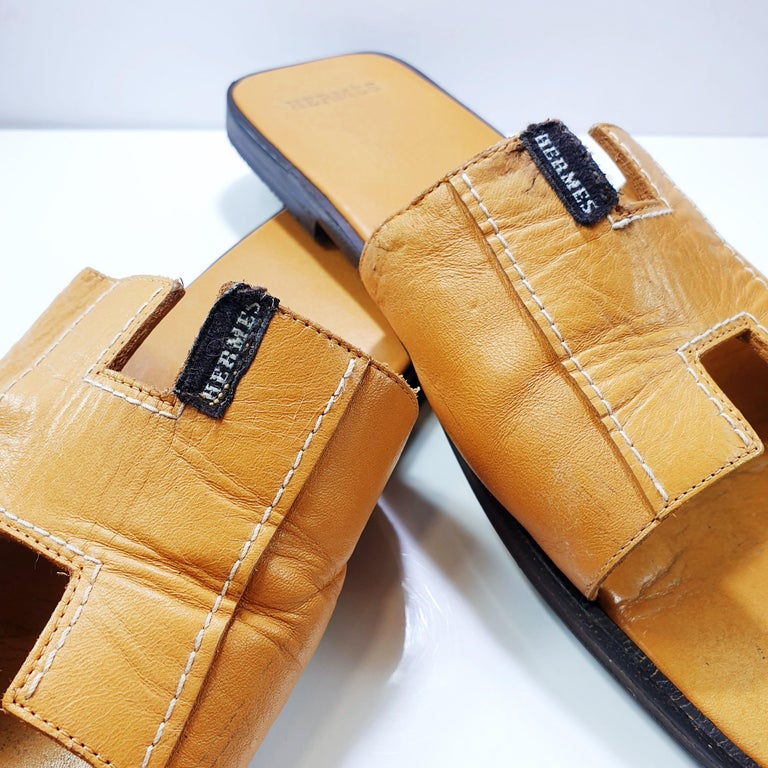 Guaranteed authentic Hermes Oran  leather slide. The iconic top stitched H cutout over the top of the foot. Blush embossed leather insole. Tone on tone wood heel with leather sole. SIZE 39.5 USA SIZE 9.5  CONDITION: Worn, recently serviced, Hermes