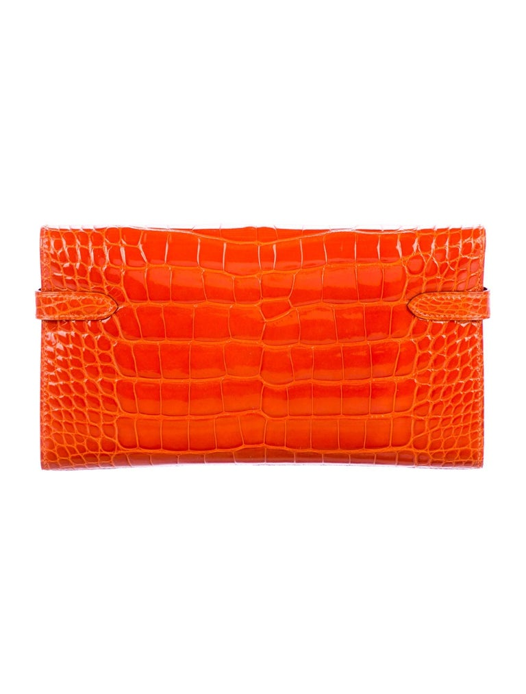 Hermes Orange Alligator Exotic Leather Palladium Silver Evening Kelly Clutch Wallet Bag in Box  Alligator  Palladium tone hardware Turnlock closure Leather lining Date code present Made in France Features zip closure, bill compartment and 12 card