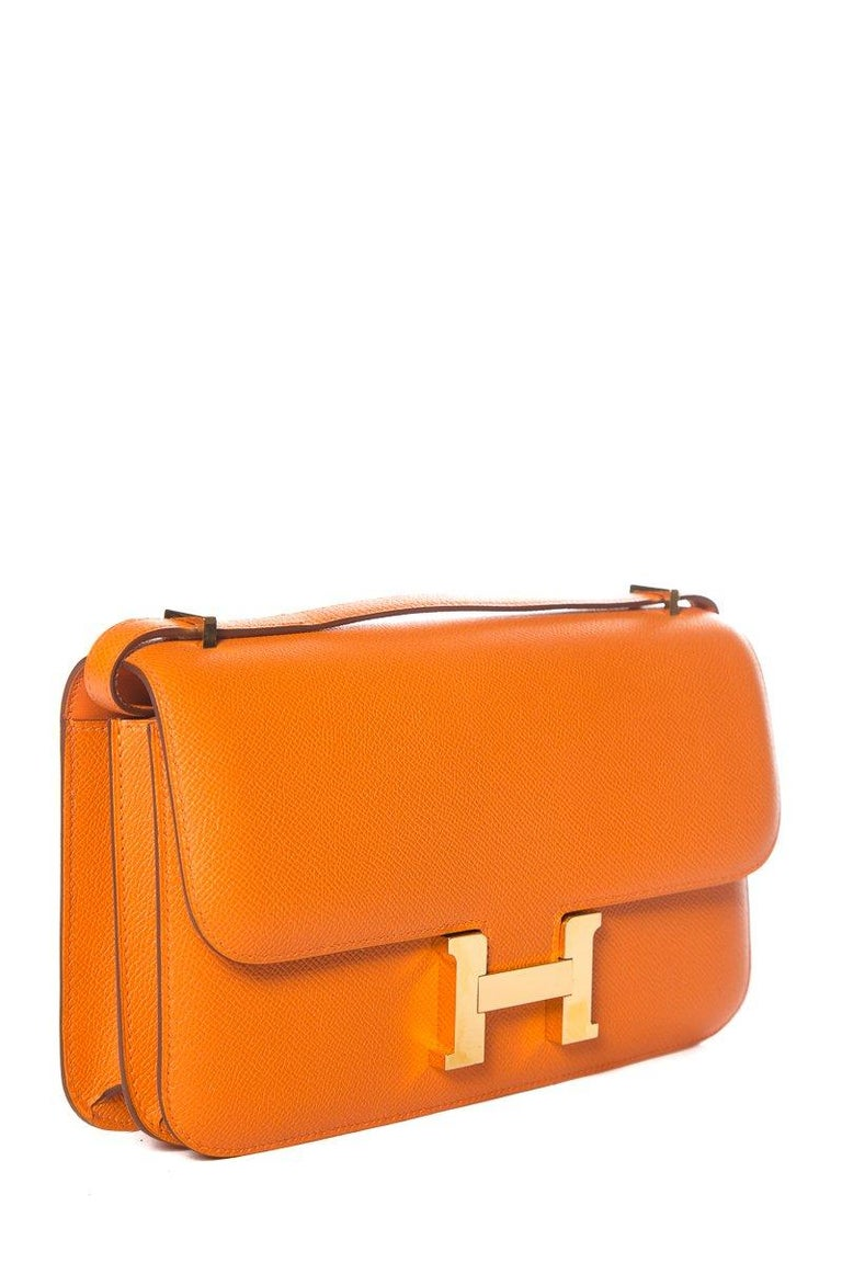 Hermes orange Epsom leather Constance with gold-plated hardware, single convertible shoulder strap, tonal leather lining, dual compartments, dual pockets at interior, and 'H' push-lock closure at front. Includes dust cover and box. This item is in